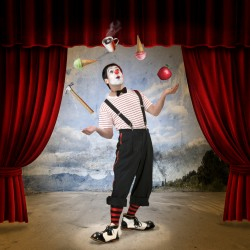 Clown performing on stage with red curtains